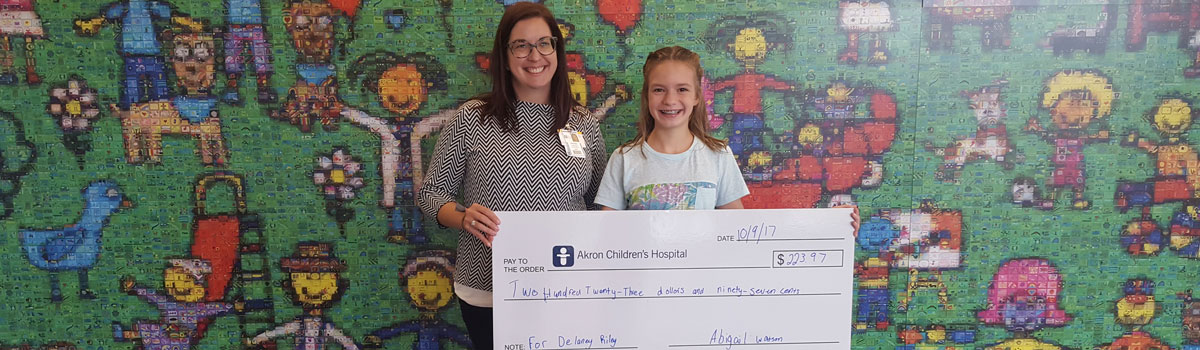 Woman and child presenting check to Akron Children's Hospital